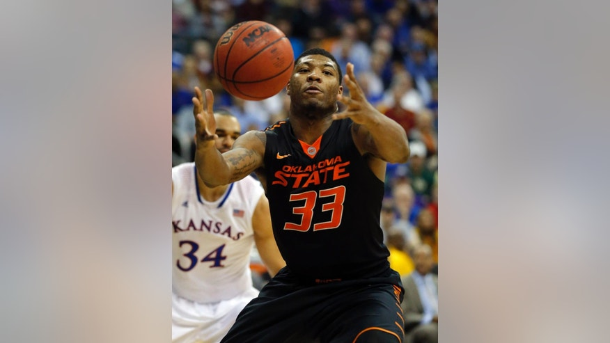 FILE - In this March 13, 2014 file photo, Oklahoma State guard Marcus Smart (33) reaches for the ball during the second half of an NCAA college basketball game against Kansas in the quarterfinals of the Big 12 Conference men's tournament in Kansas City, Mo.  Oklahoma State (21-12), the No. 9 seed in the West Region, will play No. 8 seed Gonzaga (28-6) Friday, March 21, 2014, in San Diego in its NCAA tournament opener. This will be Smart's last shot at tournament success because he will enter the NBA Draft after this season.(AP Photo/Orlin Wagner, File)