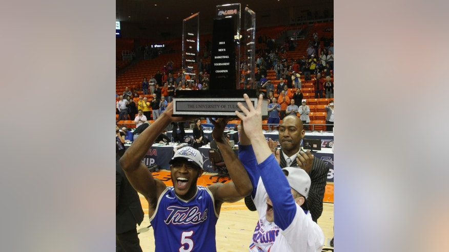 Tulsa Tim Peete, left, and Barrett Hunter, right, celebrate with the trophy as coach Danny Manning, background, claps after  their 69-60 win over  Louisiana Tech an NCAA college basketball game in the championship of the Conference USA tournament Saturday, March 15, 201,  in El Paso, Texas. (AP Photo/Victor Calzada)