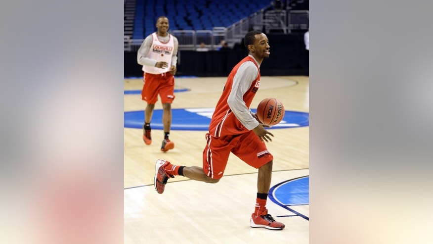 Louisville's Russ Smith, right, takes the ball to the basket during practice for the NCAA men's college basketball tournament in Orlando, Fla., Wednesday, March 19, 2014. Louisville plays against Manhattan in a second-round game on Thursday. (AP Photo/John Raoux)