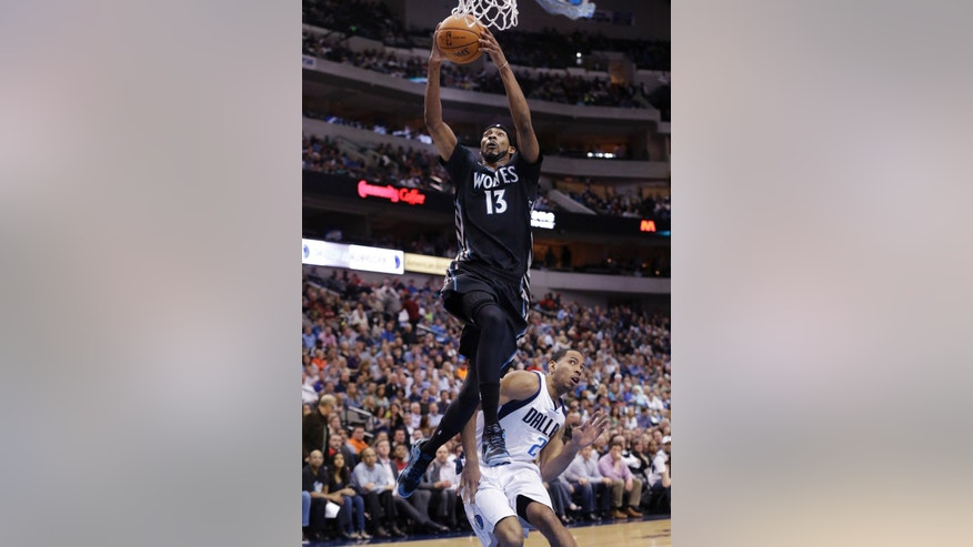 Minnesota Timberwolves forward Corey Brewer (13) scores a basket against Dallas Mavericks guard Devin Harris (20) during the first half an NBA basketball game Wednesday, March 19, 2014, in Dallas. (AP Photo/LM Otero)