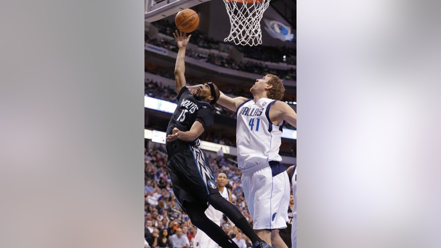 Minnesota Timberwolves forward Corey Brewer (13) drives against Dallas Mavericks forward Dirk Nowitzki (41) of Germany during the first half an NBA basketball game Wednesday, March 19, 2014, in Dallas. (AP Photo/LM Otero)