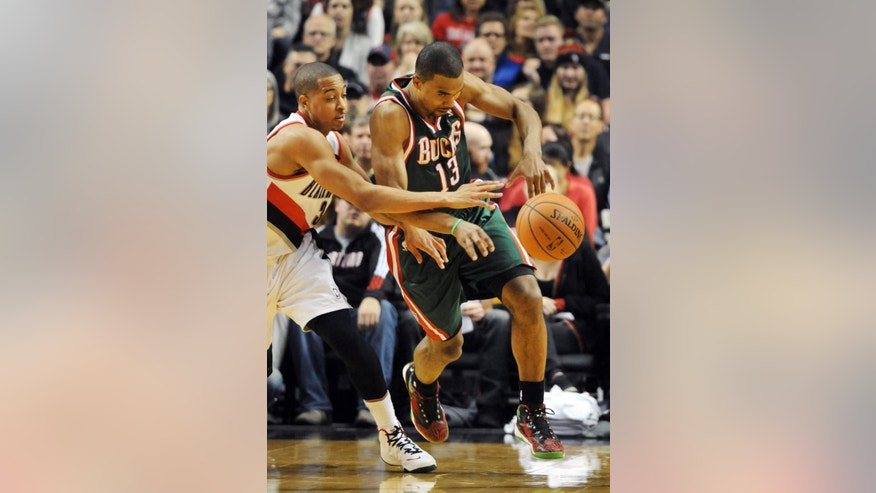 Portland Trail Blazers guard C.J. McCollum (3) tries to knock the ball away from Milwaukee Bucks guard Ramon Sessions (13) during the first half of an NBA basketball game in Portland, Ore., Tuesday, March 18, 2014. (AP Photo/Steve Dykes)
