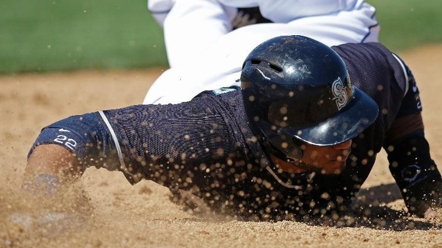 Seattle Mariners' Robinson Cano dives back to first base during the third inning of a spring exhibition baseball game against the Milwaukee Brewers, Wednesday, March 19, 2014, in Peoria, Ariz. (AP Photo/Darron Cummings)
