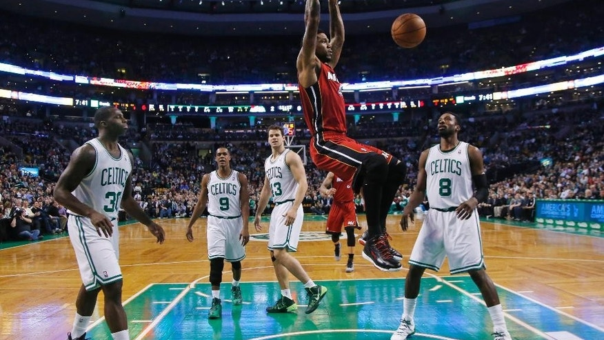 Miami Heat forward Udonis Haslem (40) dunks as Boston Celtics forward Brandon Bass (30), guard Rajon Rondo (9), center Kris Humphries (43) and forward Jeff Green (8) watch in the first quarter of an NBA basketball game in Boston Wednesday, March 19, 2014. (AP Photo/Elise Amendola)