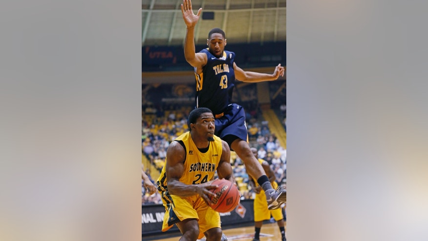 Southern Mississippi guard Michael Craig (24) looks for a shot as Toledo forward Matt Smith (43) leaps during the first half of an NCAA college basketball game in the first round of the NIT, in Hattiesburg, Miss., Wednesday, March 19, 2014. (AP Photo/Rogelio V. Solis)