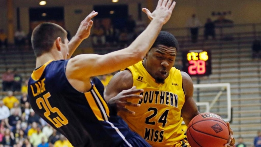 Southern Mississippi guard Michael Craig (24) knocks over Toledo guard Jordan Lauf (25) during the first half of an NCAA college basketball game in the first round of the NIT in Hattiesburg, Miss., Wednesday, March 19, 2014. (AP Photo/Rogelio V. Solis)