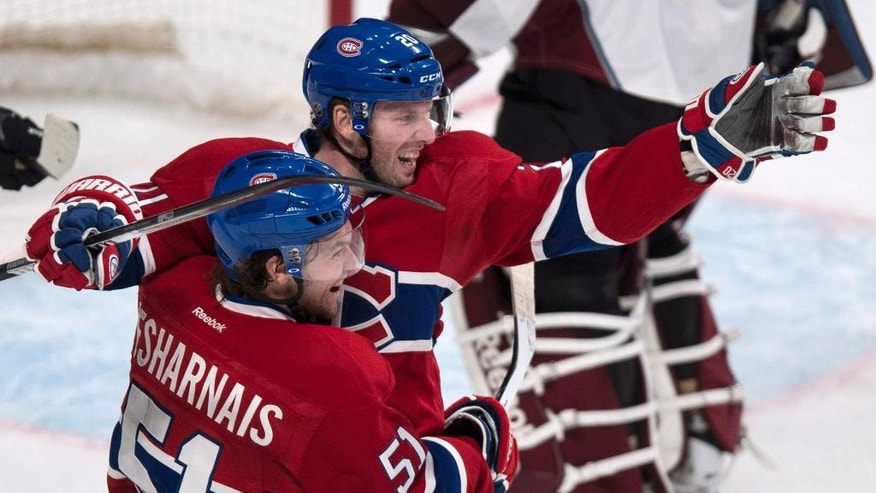 Montreal Canadiens' Thomas Vanek celebrates his third goal agaisnt the Colorado Avalanche with teamate David Desharnais during third period NHL hockey action Tuesday, March 18, 2014 in Montreal. The Canadiens beat the Avalanche 6-3. (AP Photo/The Canadian Press, Paul Chiasson)