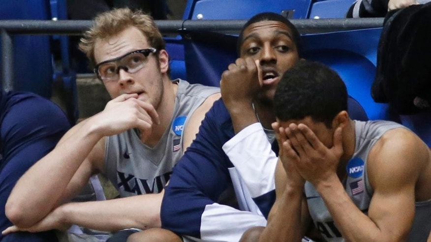 Xavier players, left to right, Matt Stainbrook, James Farr, and Dee Davis sit on the bench in the closing minute of the team's 74-59 loss to North Carolina State in a first-round game of the NCAA college basketball tournament, Tuesday, March 18, 2014, in Dayton, Ohio. (AP Photo/Al Behrman)
