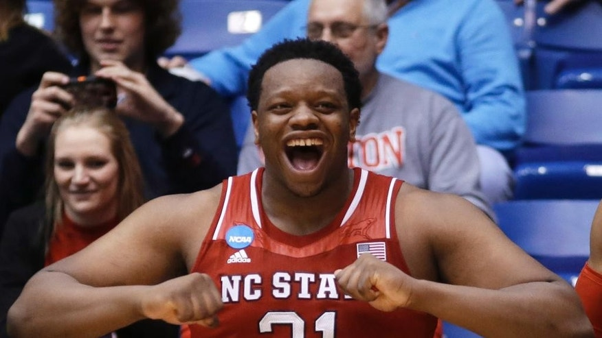 North Carolina State forward Beejay Anya celebrates on the bench in the closing seconds of the team's 74-59 win over Xavier in a first-round game of the NCAA college basketball tournament, Tuesday, March 18, 2014, in Dayton, Ohio. (AP Photo/Al Behrman)