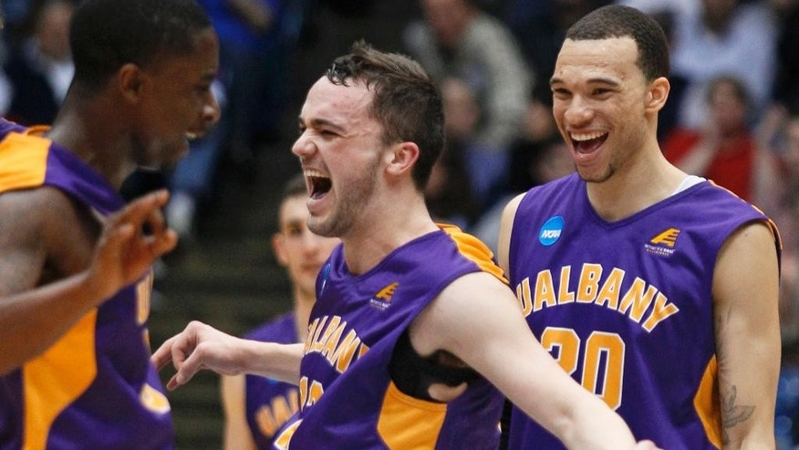 Albany guard Peter Hooley, center, celebrates with guard D.J. Evans, left, and forward Gary Johnson after Albany defeated Mount St. Mary's 71-64 in a first-round game of the NCAA college basketball tournament, Tuesday, March 18, 2014, in Dayton, Ohio. (AP Photo/Skip Peterson)