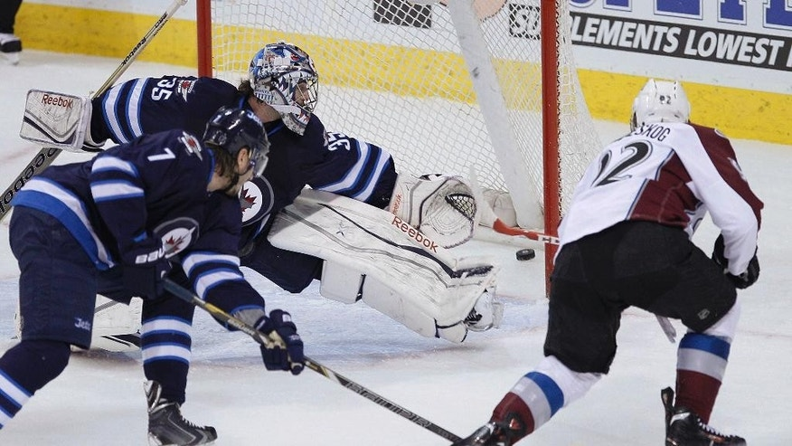 Colorado Avalanche's Gabriel Landeskog (92) rips the puck past Winnipeg Jets' goaltender Al Montoya (35) for a goal as Jets' Keaton Ellerby (7) defends during the first period of an NHL hockey game Wednesday, March 19, 2014, in Winnipeg, Manitoba. (AP Photo/The Canadian Press, John Woods)