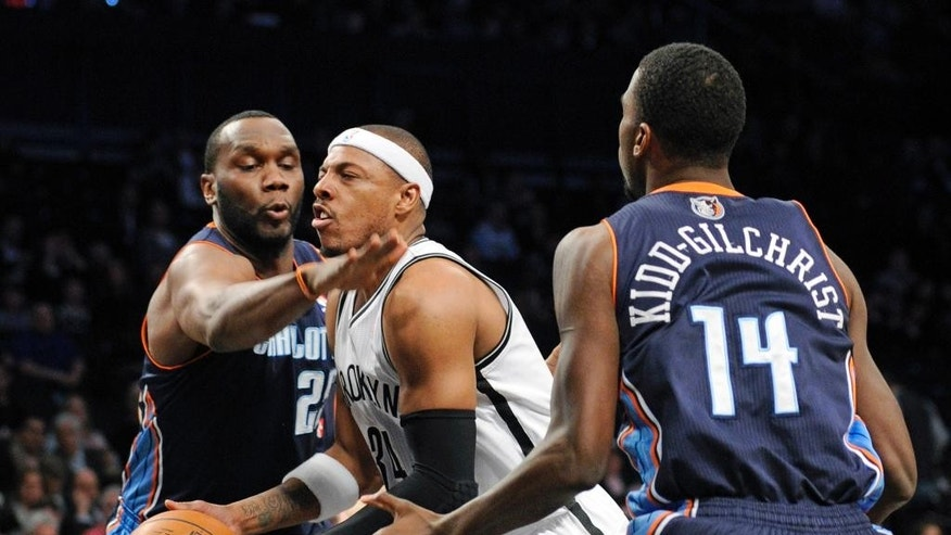 Brooklyn Nets' Paul Pierce splits the defense of Charlotte Bobcats' Al Jefferson, left, and Michael Kidd-Gilshrice, right, during the first quarter of an NBA basketball game Wednesday, March 19, 2014, at Barclay's Center in New York. (AP Photo/Bill Kostroun)