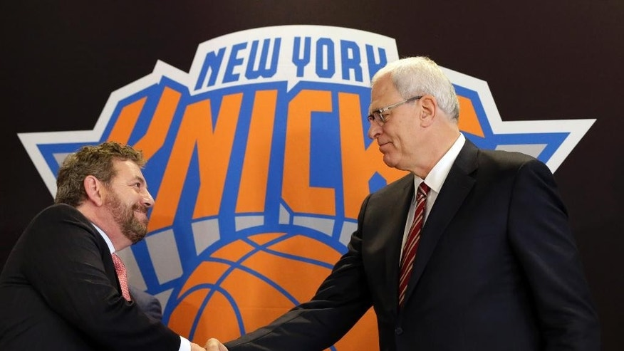 New York Knicks new team president Phil Jackson, right, shakes hands with Madison Square Garden Chairman James Dolan during a news conference where he was introduced, at New York's Madison Square Garden, Tuesday, March 18, 2014. (AP Photo/Richard Drew)
