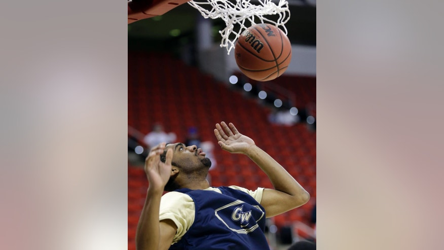George Washington's Maurice Creek watches his dunk during practice at the NCAA college basketball tournament in Raleigh, N.C., Thursday, March 20, 2014. George Washington plays Memphis in a second-round game on Friday. (AP Photo/Gerry Broome)