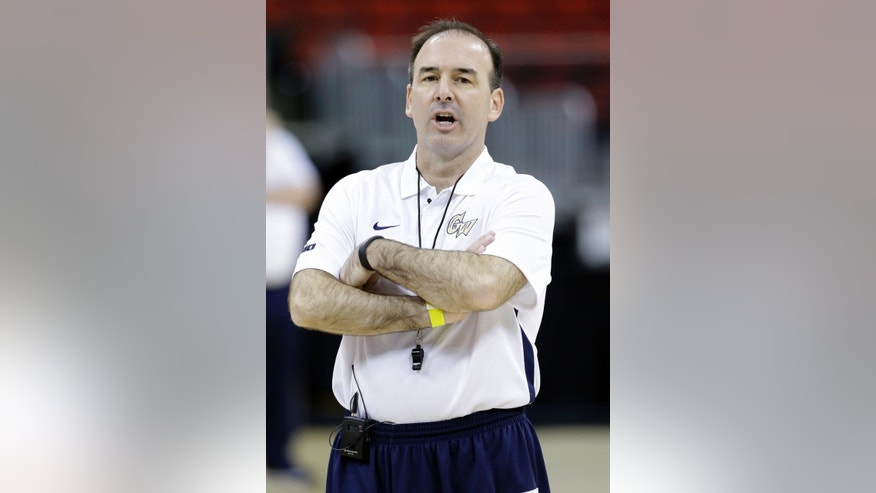 George Washington head coach Mike Lonergan directs his team during practice at the NCAA college basketball tournament in Raleigh, N.C., Thursday, March 20, 2014. George Washington plays Memphis in a second-round game on Friday. (AP Photo/Gerry Broome)
