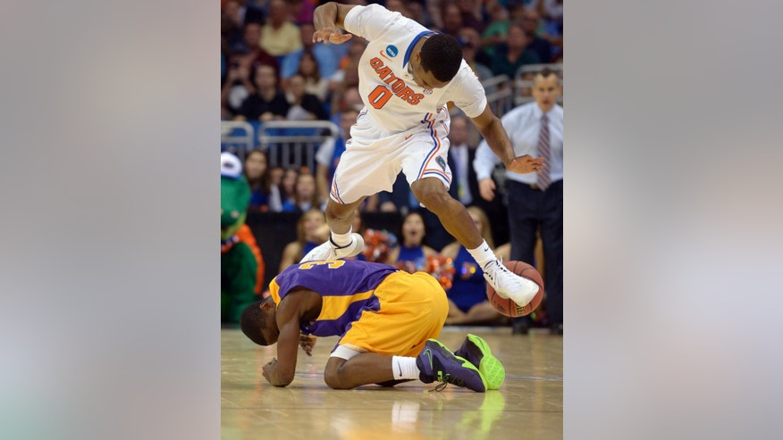 Florida guard Kasey Hill (0) and Albany guard DJ Evans (3) collide after chasing a loose ball during the second half in a second-round game in the NCAA college basketball tournament Thursday, March 20, 2014, in Orlando, Fla. Florida won 67-55. (AP Photo/Phelan M. Ebenhack)
