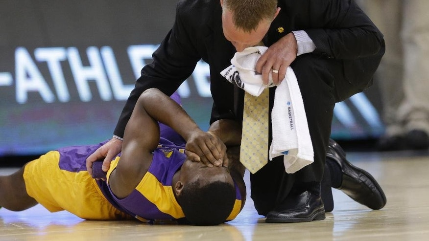 Albany guard DJ Evans (3) is attended after getting injured during the second half in a second-round game against Florida in the NCAA college basketball tournament Thursday, March 20, 2014, in Orlando, Fla. Florida defeated Albany 67-55. (AP Photo/John Raoux)