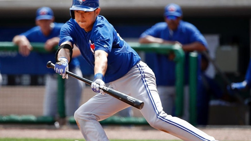 Toronto Blue Jays shortstop Munenori Kawasaki lays down a bunt, a second-inning bunt ground out, in a spring exhibition baseball game against the Philadelphia Phillies in Clearwater, Fla., Thursday, March 20, 2014.  (AP Photo/Kathy Willens)