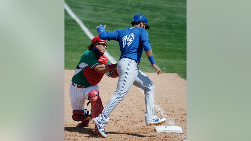 Toronto Blue Jays' Jose Bautista (19) is picked off at first by Philadelphia Phillies catcher Carlos Ruiz (51) in the sixth inning of a spring exhibition baseball game in Clearwater, Fla., Thursday, March 20, 2014.  The Jays defeated the Phillies 3-1. (AP Photo/Kathy Willens)