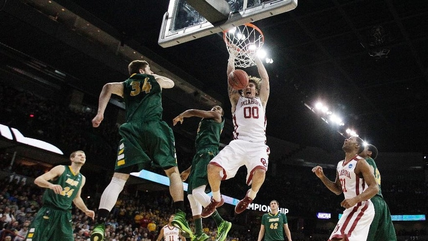 Oklahoma's Ryan Spangler (00) dunks against North Dakota State's Chris Kading (34) and Kory Brown during the second half in a second-round game in the NCAA men's college basketball tournament in Spokane, Wash., Thursday, March 20, 2014. (AP Photo/Young Kwak)