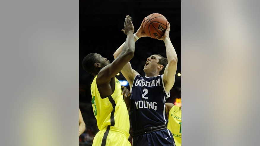 BYU guard Matt Carlino (2) drives to the basket against Oregon forward Richard Amardi (13) during the first half of a second-round game in the NCAA college basketball tournament Thursday, March 20, 2014, in Milwaukee. (AP Photo/Morry Gash)