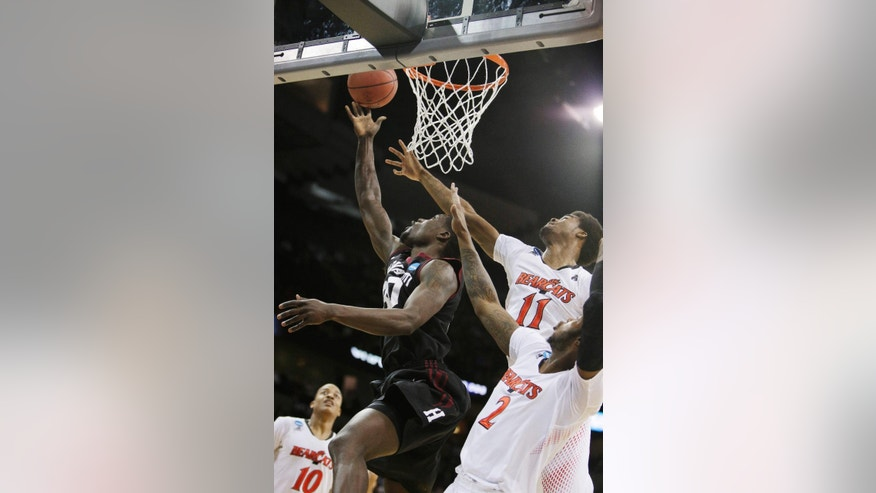 Harvard's Kyle Casey (30) attempts a layup against Cincinnati's Jermaine Lawrence (11) and Titus Rubles (2) in the first half during the second-round game of the NCAA college basketball tournament in Spokane, Wash., Thursday, March 20, 2014. (AP Photo/Young Kwak)