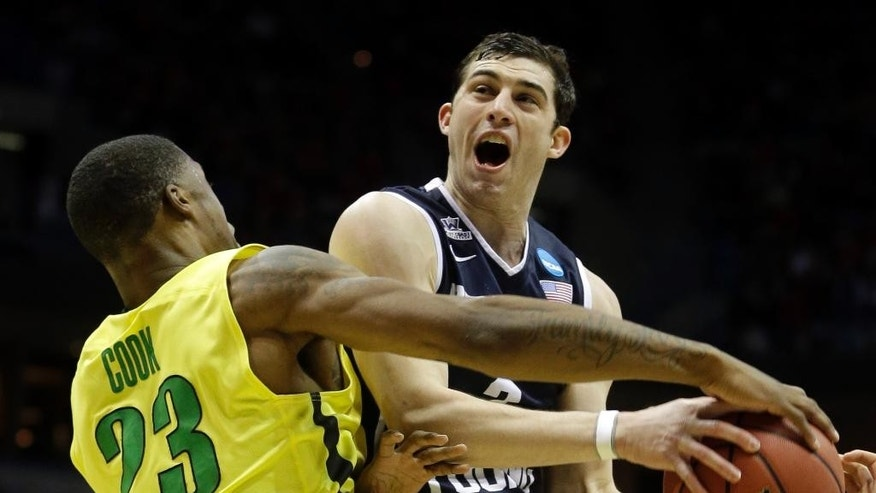 BYU guard Matt Carlino is fouled by Oregon forward Elgin Cook (23) during the first half of a second-round game in the NCAA college basketball tournament Thursday, March 20, 2014, in Milwaukee. (AP Photo/Morry Gash)