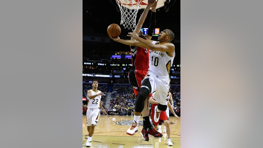 New Orleans Pelicans guard Eric Gordon (10) drives to the basket against Toronto Raptors guard Nando de Colo (3) during the first half of an NBA basketball game in New Orleans, Wednesday, March 19, 2014. (AP Photo/Jonathan Bachman)