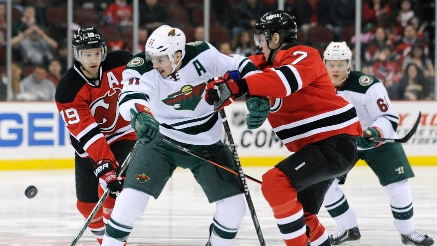 Minnesota Wild's Zach Parise is sandwiched by New Jersey Devils' Travis Zajac, left, and Mark Fayne, right, during the first period of an NHL hockey game Thursday, March 20, 2014, in Newark, N.J. (AP Photo/Bill Kostroun)