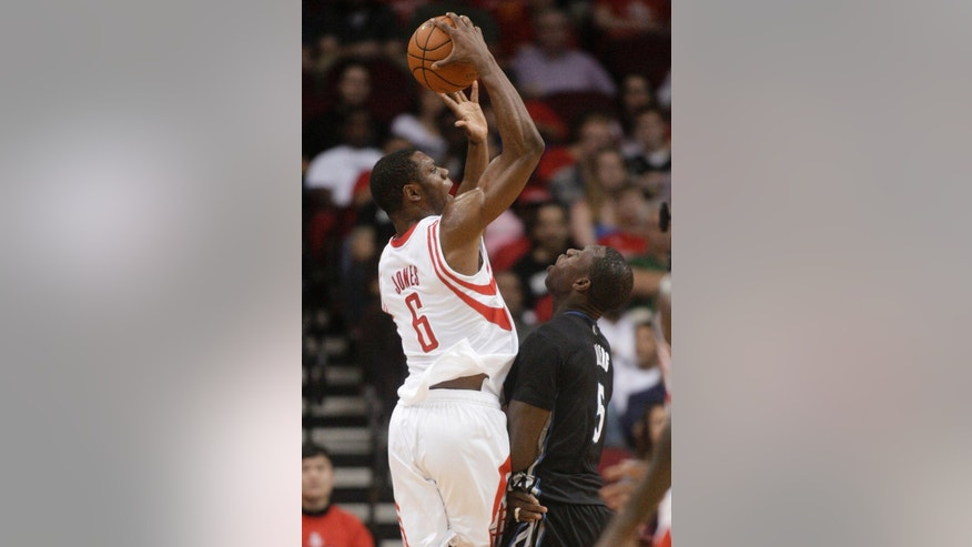 Houston Rockets forward Terrence Jones (6) shoots over Minnesota Timberwolves center Gorgui Dieng (5) during the second quarter of an NBA basketball game, Thursday, March 20, 2014, in Houston. (AP Photo/Patric Schneider)