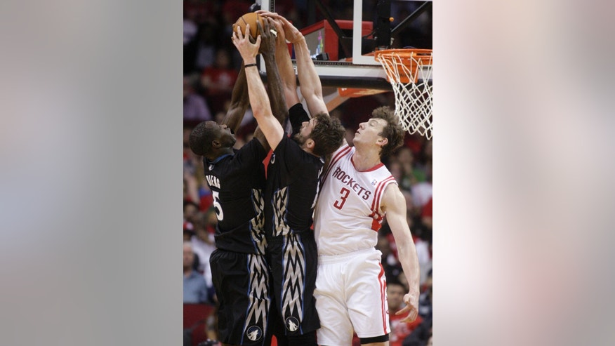 Minnesota Timberwolves' Gorgui Dieng (5) and Kevin Love bring down a rebound against Houston Rockets' Omer Asik (3) during the second quarter of an NBA basketball game, Thursday, March 20, 2014, in Houston. (AP Photo/Patric Schneider)