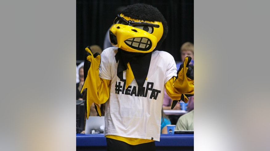 """Herky,"" the Iowa mascot, wears a T-shirt supporting Pat McCaffery, son of Iowa head coach Fran McCaffery, at halftime of a first-round game against Tennessee in the NCAA college basketball tournament on Wednesday, March 19, 2014, in Dayton, Ohio. Coach McCaffery flew home to be with his 13-year-old son who had a tumor removed Wednesday morning and then flew back to Dayton for their game against Tennessee. (AP Photo/Al Behrman)"