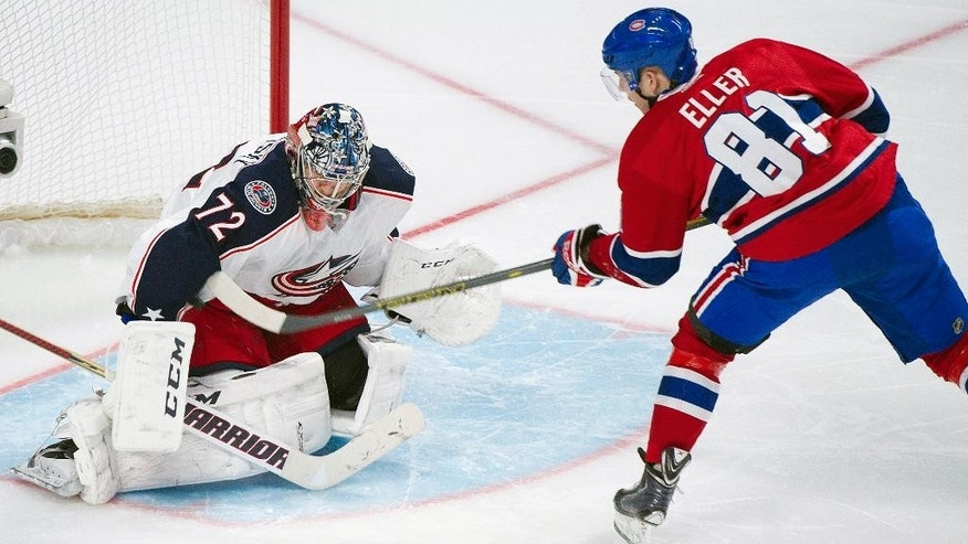 Columbus Blue Jackets' goaltender Sergei Bobrovsky, left, stops a penalty shot against Montreal Canadiens' Lars Eller during the third period of an NHL hockey game in Montreal, Thursday, March 20, 2014. (AP Photo/The Canadian Press, Graham Hughes)
