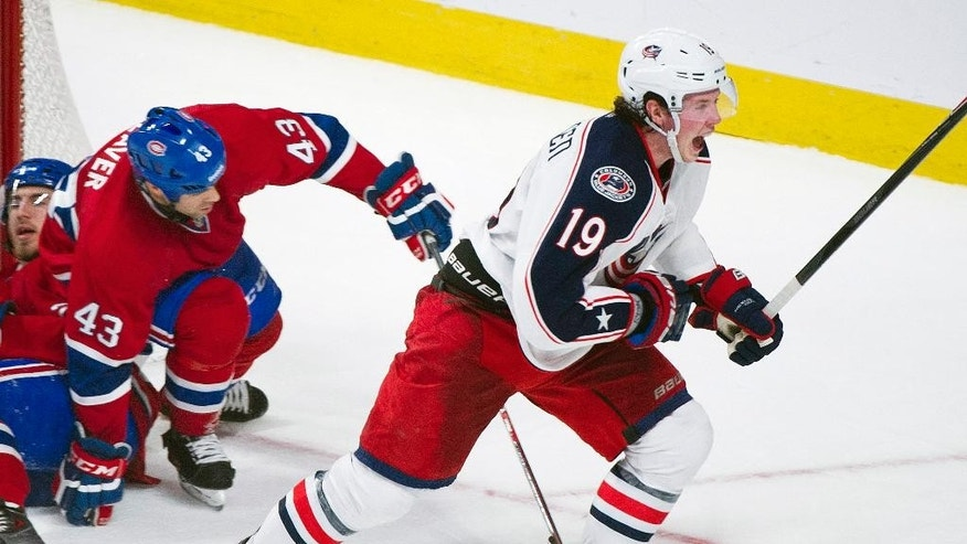 Columbus Blue Jackets' Ryan Johansen, right, celebrates after scoring against the Montreal Canadiens as Canadiens' Jarred Tinordi, left, and Mike Weaver defend during the third period of an NHL hockey game in Montreal, Thursday, March 20, 2014.  (AP Photo/The Canadian Press, Graham Hughes)