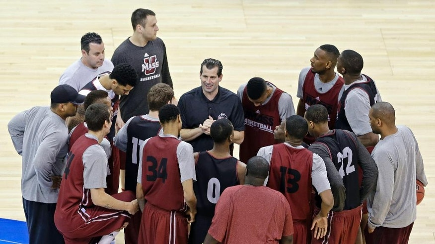 Massachusetts head coach Derek Kellogg, center, talks with his team during practice at the NCAA college basketball tournament in Raleigh, N.C., Thursday, March 20, 2014. Massachusetts plays Tennessee in a second-round game on Friday. (AP Photo/Gerry Broome)