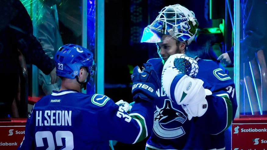 Vancouver Canucks' Henrik Sedin, left, and goalie Eddie Lack, both of Sweden, celebrate their 2-0 win over the Nashville Predators during an NHL hockey game in Vancouver, British Columbia, on Wednesday, March 19, 2014. (AP Photo/The Canadian Press, Darryl Dyck)