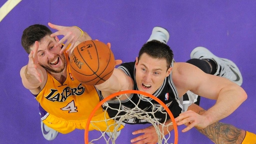 San Antonio Spurs forward Aron Baynes, right, of Australia, reaches for a rebound along with Los Angeles Lakers forward Ryan Kelly during the first half of their NBA basketball game, Wednesday, March 19, 2014, in Los Angeles. (AP Photo/Mark J. Terrill)