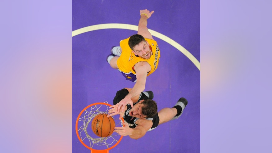 San Antonio Spurs center Tiago Splitter, of Brazil, below, dunks as Los Angeles Lakers forward Ryan Kelly defends during the first half of an NBA basketball game, Wednesday, March 19, 2014, in Los Angeles. (AP Photo/Mark J. Terrill)