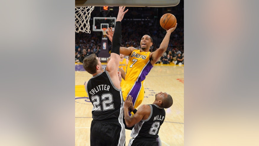 Los Angeles Lakers forward Xavier Henry, right, puts up a shot as San Antonio Spurs center Tiago Splitter, left, of Brazil, and guard Patty Mills, of Australia, defend during the first half of an NBA basketball game, Wednesday, March 19, 2014, in Los Angeles. (AP Photo/Mark J. Terrill)