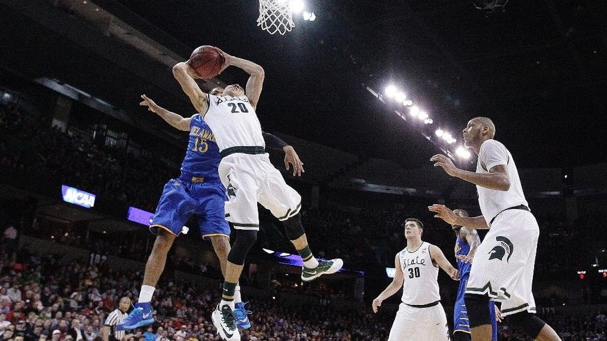 Michigan State's Travis Trice (20) shoots in front of Delaware's Maurice Jeffers (15) in the first half of a second-round of the NCAA men's college basketball tournament in Spokane, Wash., Thursday, March 20, 2014. (AP Photo/Young Kwak)
