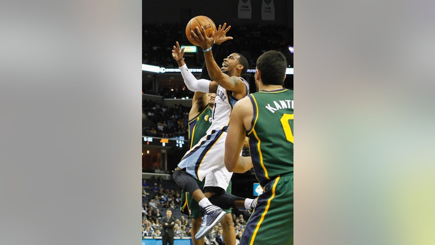 Memphis Grizzlies guard Mike Conley (11) drives to the basket between Utah Jazz guard Trey Burke, back, and center Enes Kanter (0), of Turkey, in the first half of an NBA basketball game  onWednesday, March 19, 2014, in Memphis, Tenn. (AP Photo/Lance Murphey)