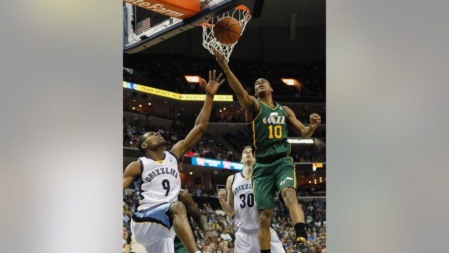 Utah Jazz guard Alec Burks (10) reaches for a rebound over Memphis Grizzlies guard Tony Allen (9) in the first half of an NBA basketball game on Wednesday, March 19, 2014, in Memphis, Tenn. (AP Photo/Lance Murphey)