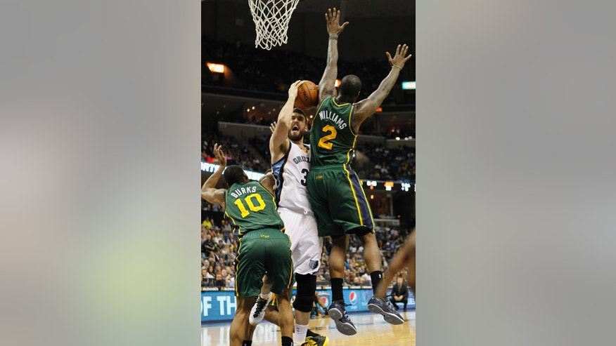 Memphis Grizzlies center Marc Gasol (33), of Spain, goes to the basket against Utah Jazz guard Alec Burks (10) and forward Marvin Williams (2) in the first half of an NBA basketball game on Wednesday, March 19, 2014, in Memphis, Tenn. (AP Photo/Lance Murphey)