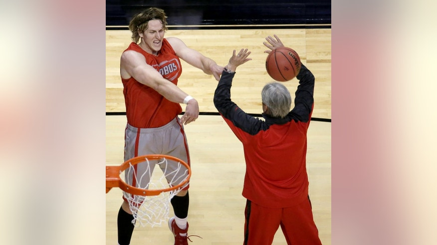 New Mexico's Cameron Bairstow passes around head coach Craig Neal, right, during practice for the NCAA college basketball tournament Thursday, March 20, 2014, in St. Louis. New Mexico is scheduled to play against Stanford in a second-round game on Friday. (AP Photo/Charlie Riedel)