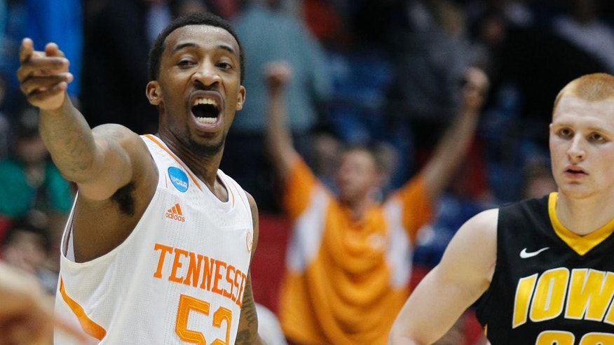 Tennessee guard Jordan McRae (52) motions to a teammate while Iowa forward Aaron White (30) watches in overtime of a first-round game of the NCAA college basketball tournament, Wednesday, March 19, 2014, in Dayton, Ohio. McRae led Tennessee to a 78-65 win with 20 points. (AP Photo/Skip Peterson)