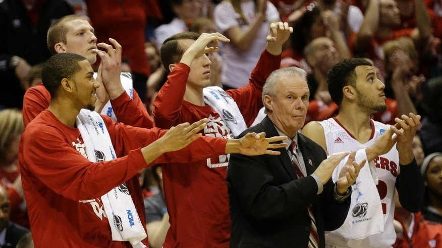 Wisconsin head coach Bo Ryan and players on the bench react for a three pointer shot by Wisconsin guard Ben Brust during the second half of a second-round game in the NCAA college basketball tournament Thursday, March 20, 2014, in Milwaukee. (AP Photo/Jeffrey Phelps)