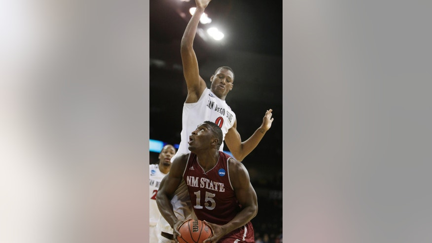New Mexico State's Tshilidzi Nephawe (15) prepares to take a shot against San Diego State's Skylar Spencer (0) during overtime during the second-round game of the NCAA men's college basketball tournament in Spokane, Wash., Thursday, March 20, 2014. San Diego State won 73-69 in overtime. (AP Photo/Young Kwak)