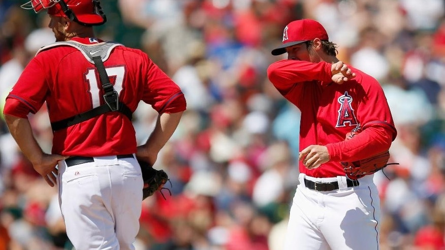 Los Angeles Angels' C.J. Wilson, right, wipes his face as he gets a visit from catcher Chris Iannetta after giving up a run to the Kansas City Royals during the first inning of a spring training baseball game Friday, March 21, 2014, in Tempe, Ariz. (AP Photo/Ross D. Franklin)