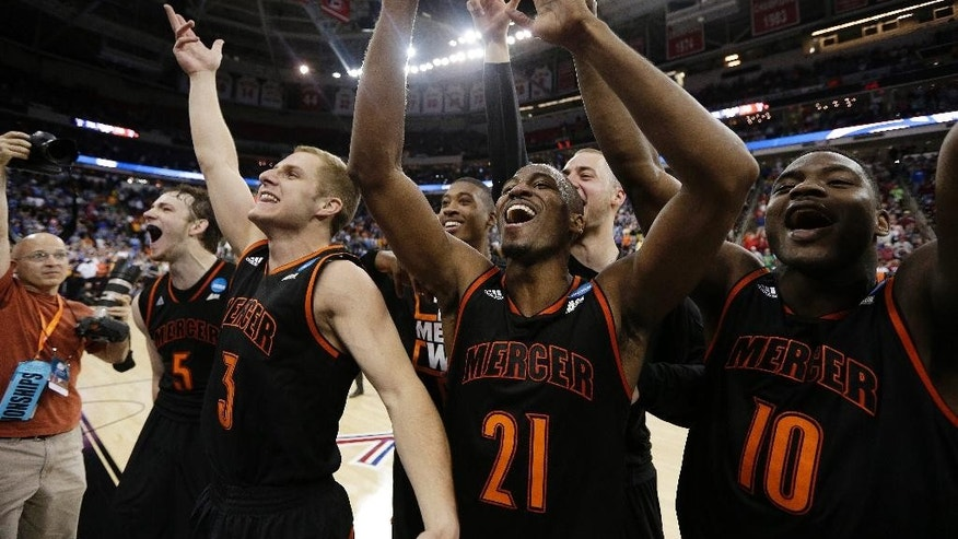 Mercer guard Langston Hall (21) and other Mercer players celebrate after the second half of an NCAA college basketball second-round game against Duke, Friday, March 21, 2014, in Raleigh, N.C. Mercer won 78-71. (AP Photo/Chuck Burton)