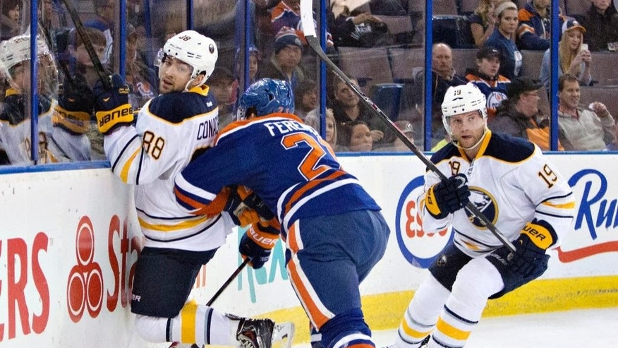 Buffalo Sabres' Cory Conacher (88) is checked by Edmonton Oilers' Andrew Ference (21) as Cody Hodgson (19) looks for the puck during the first period of an NHL hockey game in Edmonton, Alberta, on Thursday, March 20, 2014. (AP Photo/The Canadian Press, Jason Franson)